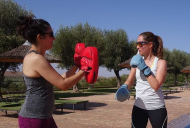 Two women boxing by a pool