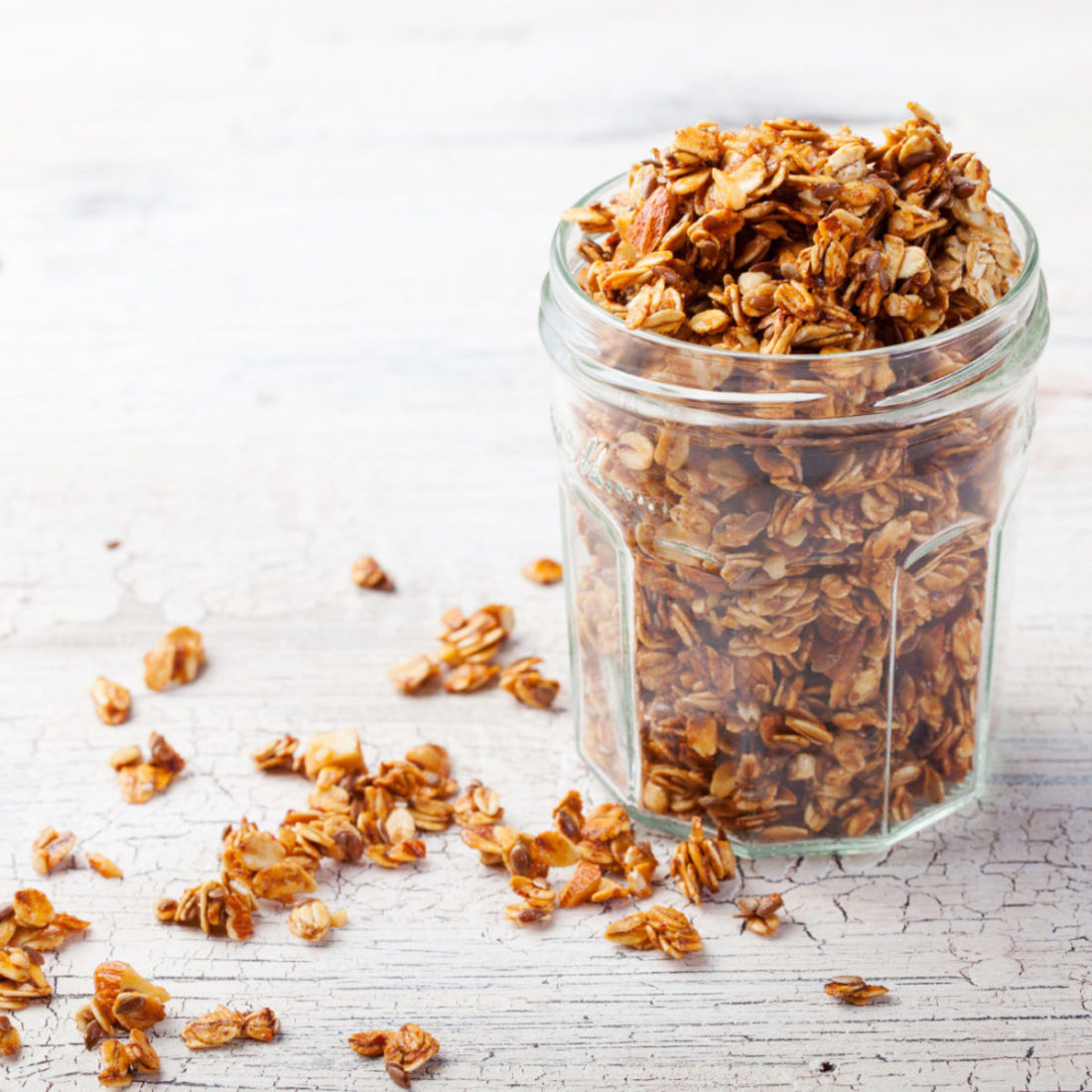 Healthy breakfast. Fresh granola, muesli in a glass jar. copy space.Organic oat,almond and sunflower seeds