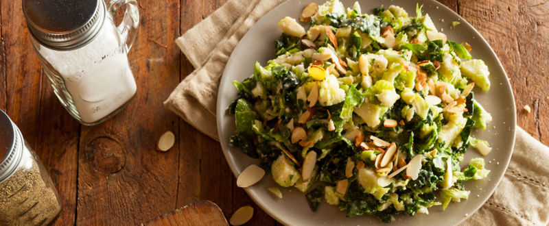 Two healthy kale salads served on a traditional table
