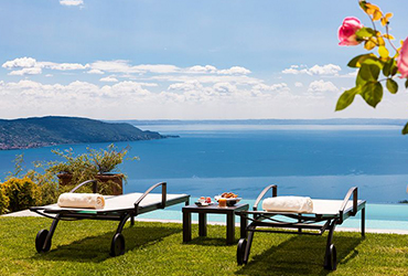 Sun loungers overlooking the ocean at Lefay resort