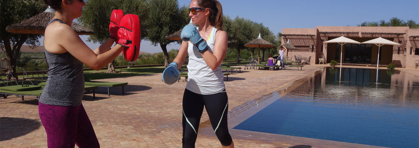 Two women personal training by the pool