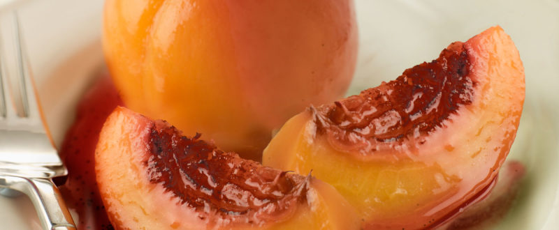 Baked peach with peach and berry sauce