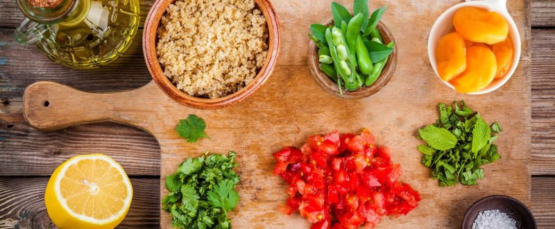 Ingredients to make tabbouli laid out on a wooden platter