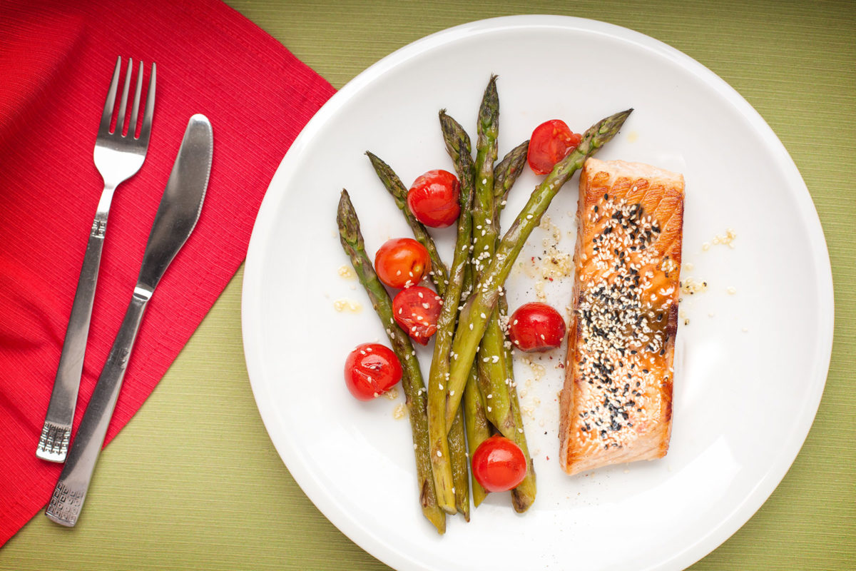 Sesame salmon served with asparagus and tomatoes
