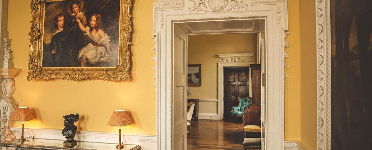 A doorway from the Drawing Room showing several oil paintings at Kirtlington Park